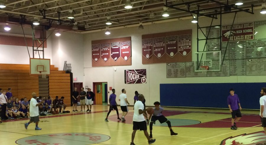 Vice Principal Mr. Porter brings the ball up the court in the first quarter, ready to attack the student defense. (Credit: Amit Dadon)