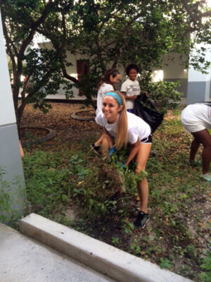 Community Clean-up. Along with her teammates from the women's varsity soccer team, senior Emma Jacobs helps pull out weeds in a planted area of the MSD courtyard. Jacobs favorite form of community service is volunteering at local soccer camps, where she can help teach kids how to play soccer.