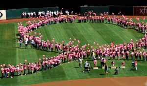 More than 350 Bay Area breast cancer survivors form a symbolic human pink ribbon on the field before the Oakland Athletics take on the Seattle Mariners at O.co Coliseum in Oakland, Calif., on Sunday, Sept. 6, 2015. The event was part of the 17th annual Oakland A's Breast Cancer Awareness Day. The A's announced that more than $75,000 was raised. (Susan Tripp Pollard/Bay Area News Group/TNS)