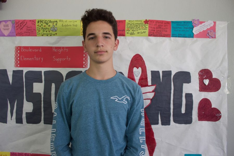 Freshman Jason Snytte poses next to an MSD Strong poster during his second week back to school. Photo by Anna Dittman