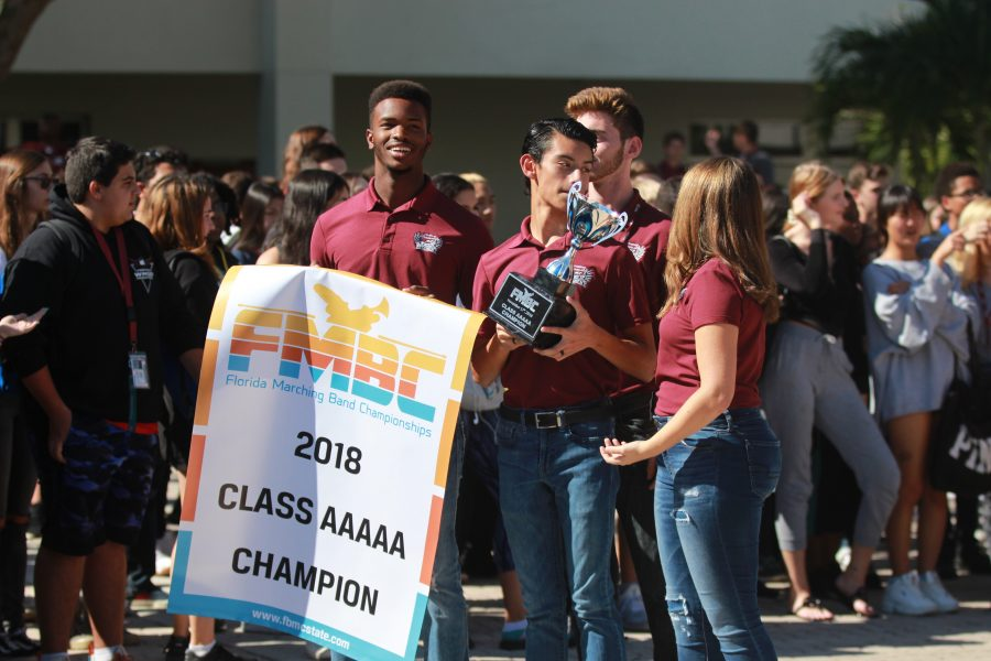 On Tuesday, Nov. 20 band officers, senior Steven Blake, juniors Nico Fraiser and Angelina Brier and sophomore Jeremy Weschler, show off their state trophies to MSD students and staff. Photo by Nyan Clarke