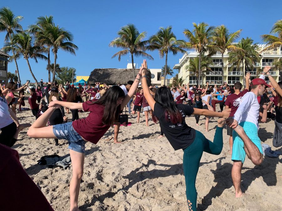 "Sunkissed Stretches. Seniors Fallon McBrien and Sophie Ayoung Chee hold parter dancer pose together at Deerfield Beach Feb. 14, 2019.  ""This was a really relaxing experience that I shared with my best friend,"" McBrien said. Photo by Zoe Gordon"