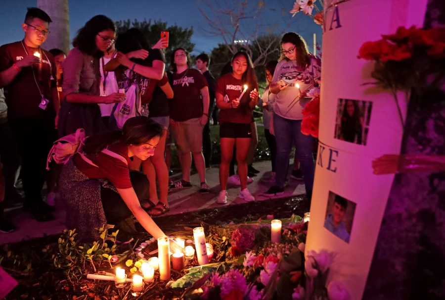 Makeshift Memorial. Senior Hannah Kapoor lights a candle after an interfaith ceremony at Pine Trails Park to remember the 17 victims killed last year at Marjory Stoneman Douglas High School, on Thursday, Feb. 14, 2019. Photo courtesy of John McCall/Sun Sentinel/TNS