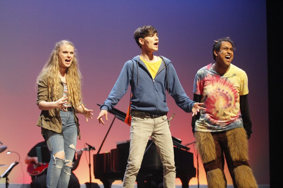 "Electrifying Performance. Juniors Isabela Barry, Tanzil Philip and senior Alexander Athanasiou perform in Douglas Drama's production of the concert version of ""The Lightning Thief"" on April 26. Photo by Mackenzie Quinn"