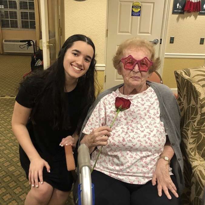 Key Club President Rachel Nattis beams at the camera with an Aston Gardens resident.