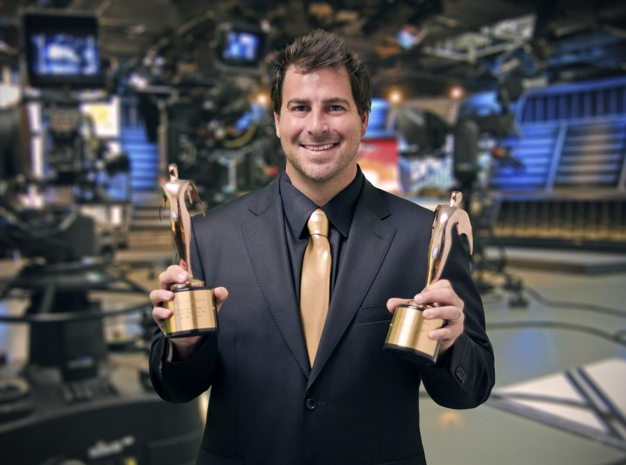 Evan Golden displays two of his awards on the set of