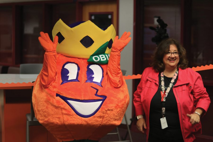 New and Improved. Media Specialist Diana Haneski, along with the mascot of the Orange Bowl Committee, Obie the Orange, welcome students and staff to enjoy the newly renovated media center on Monday, Nov. 18. In order to match the new look, the addition to the media center was named the STEAM Lab. Photo by Darian Williams