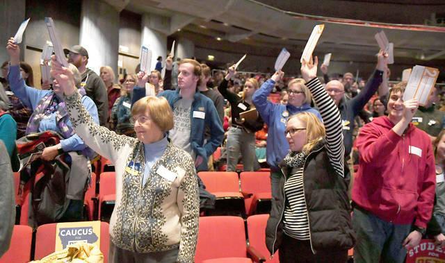 Iowa Caucus goers raise their hands. Caucus-goers raise their hands to be counted during the caucuses at Stephen Auditorium Monday, Feb. 3, 2020, in Ames, Iowa.