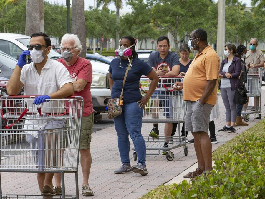 Seven out of nine customers in a long line outside Costco, wear protective masks, Friday in Royal Palm Beach. The discount wholesaler had supplies of toilet paper, paper towels, tissues, chicken, eggs and milk, but no hand sanitizer. [ALLEN EYESTONE/palmbeachpost.com]