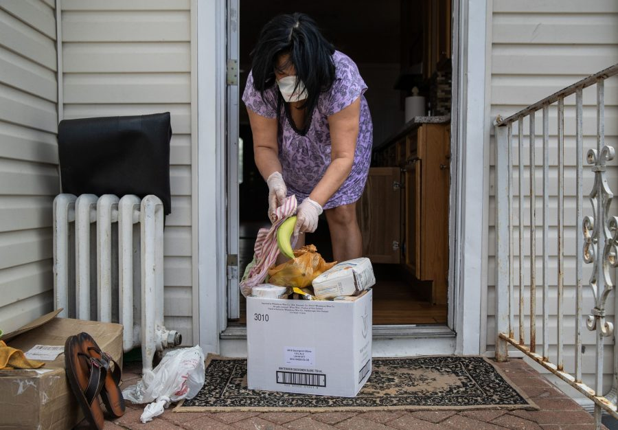 Dominican immigrant Paty Banks cleans donated groceries before bringing them into her home on April 16, 2020 in Long Island, New York. Banks said she hasn't worked in her job as a home health care worker for a month due to the coronavirus crisis. The groceries were purchased by the Democratic Socialists of America in Nassau County, Long Island.