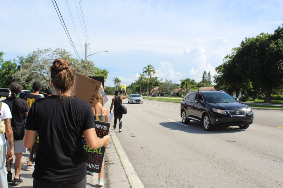 Protestors from Parkland and Coral Springs embark on a solidarity walk, making their way to Coral Springs City Hall as nearby drivers honk in support. Photo by Ashley Ferrer