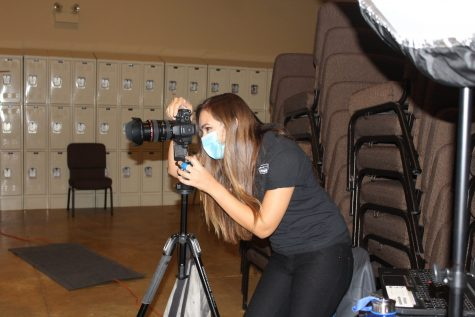 (name), Strawbridge photographer, looks through her camera to set up as incoming underclassmen will arrive