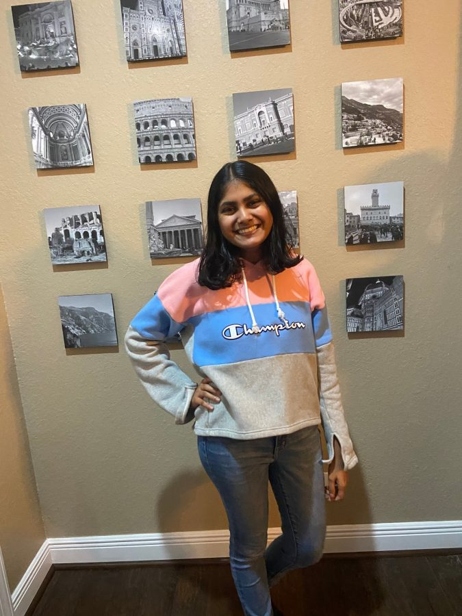 Amoli Kulkarni wears a pink, blue and grey Champion sweatshirt with light jeans.