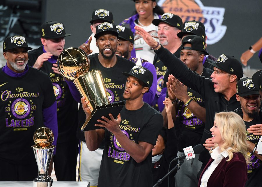 Rajon Rondo (center) holds the NBA trophy to celebrate the Lakers' NBA Finals win. He is surrounded by his teammates and sports reporters.