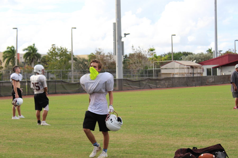 Senior Connor Lieberman walks through the field during an MSD football practice, wearing his mask as mandated by coaches.