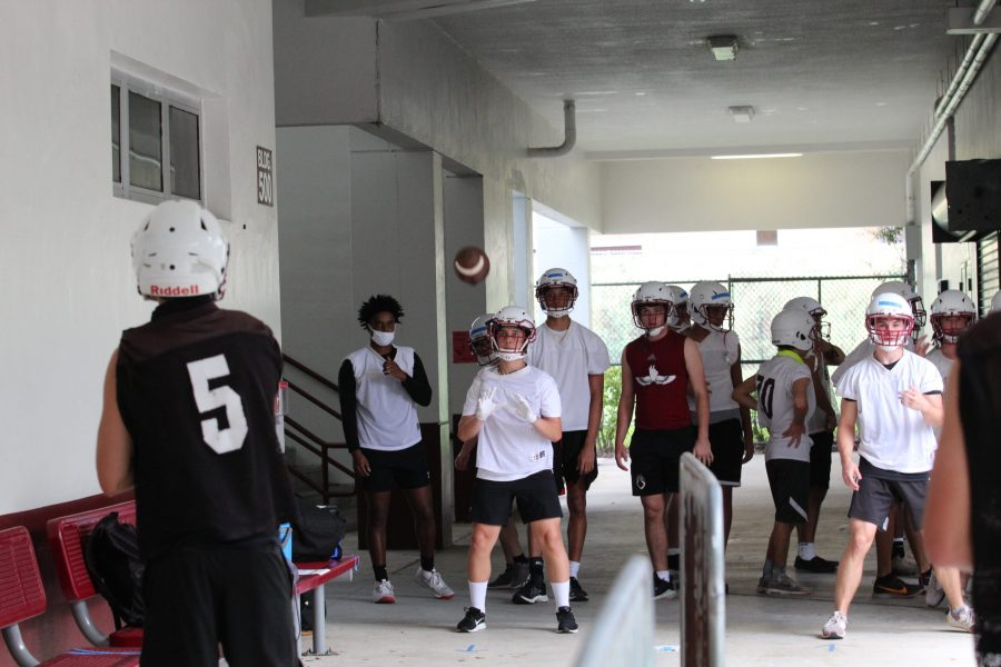 Marjory Stoneman Douglas High School football team's receiver group and quarterbacks run passing drills after school on Wednesday, Oct. 13. The team began voluntary conditioning on Sept. 21, and their first game is on Oct. 29 at Coral Springs High School. Photo by Ava Steil