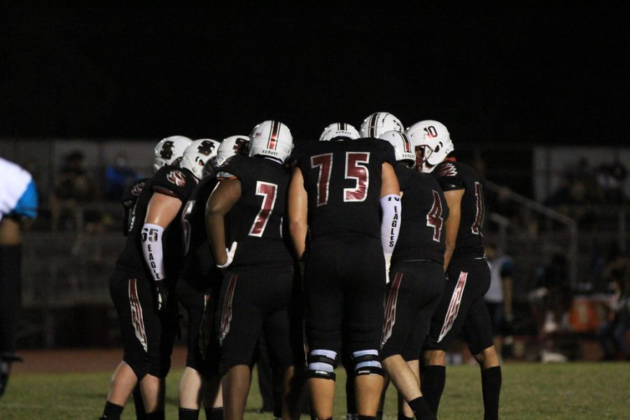 Mark Dorsett (7) and Michael Mclaughlin (75) stand in a huddled group of the MSD varsity football team as they discuss plays to run on an offensive drive at Cumber Sadium against the Coral Glades Jaguars.