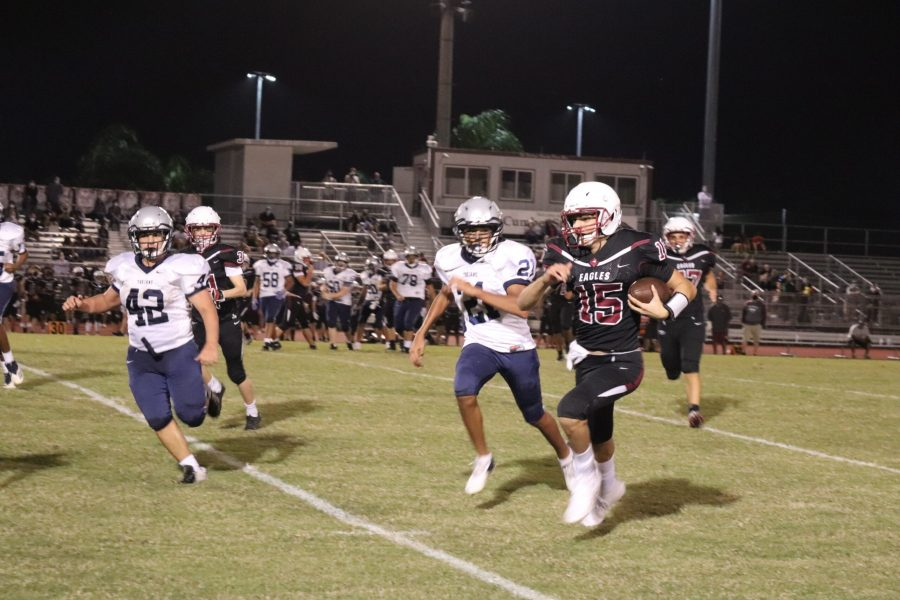 Eagles Quarterback Ryan Spallina (15) outruns the Trojans' defense to score a touchdown. Photo by Brooke Glaros.