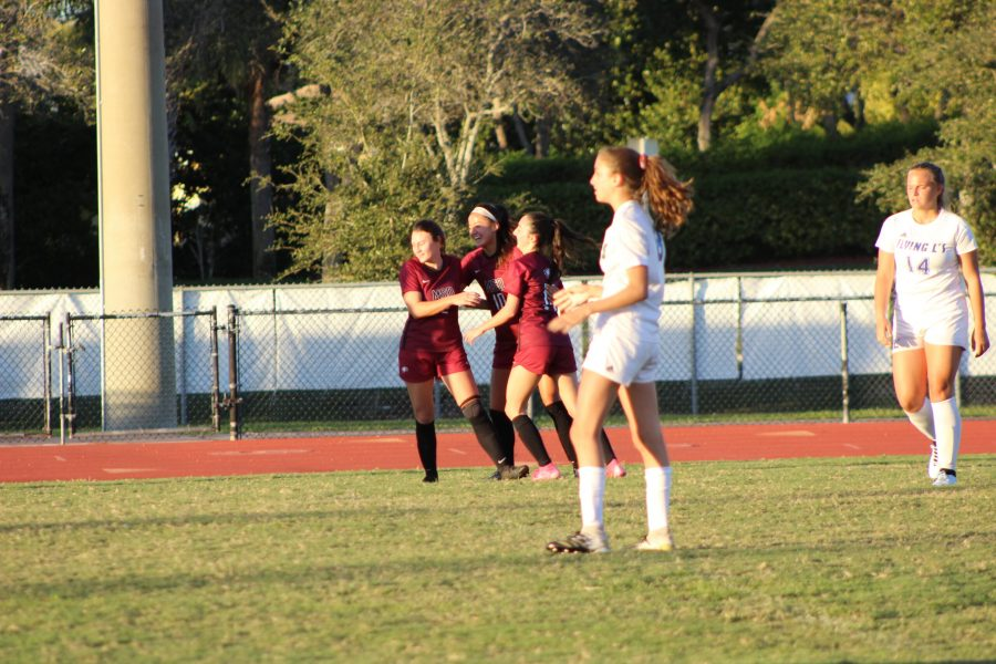 Forward Mia Engelbart (10) celebrates scoring a goal with her teammates. This was one of her two goals in the Eagles' match-up against the Flying L's. Photo by Theron Piccininni