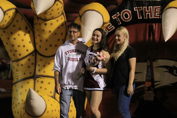 Senior Kacie Shatzkamer stands in between her parents while wearing his MSD Cheer uniform and senior sash. She is holding a bouquet of flowers. The photo was taken in front of the MSD Eagles football teams blow-up entrance.