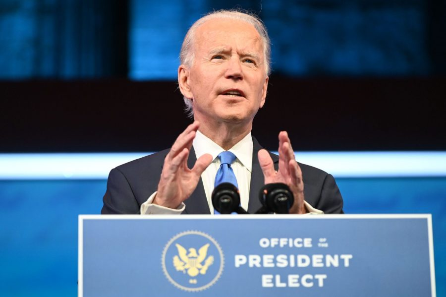 Joe Biden stands behind a speaker of the Office of the President Elect, delivering remarks.