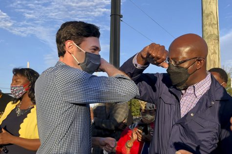 Democratic U.S. Senate candidates Jon Ossoff, right, and Raphael Warnock, left, of Georgia tap elbows during a rally for supporters on Nov. 15, 2020 in Marietta, Georgia. Both become senators Wednesday.  (Jenny Jarvie/Los Angeles Times/TNS)
