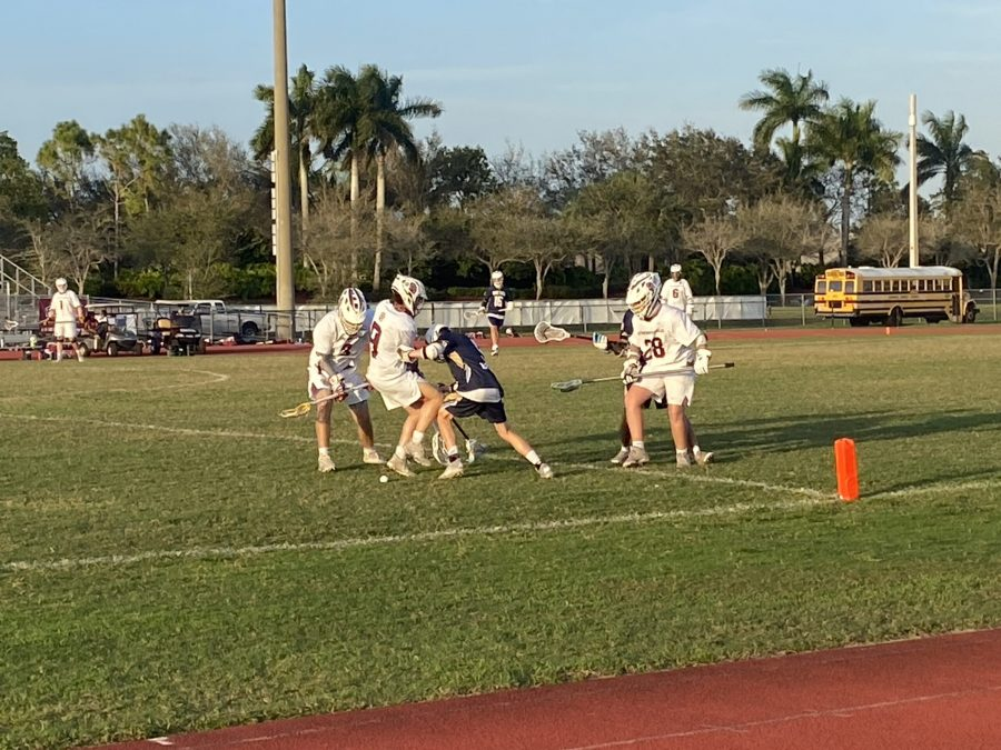 In the first half of the MSD men's varsity lacrosse matchup against West Boca High School, three players of the Eagles' offense surround an opposing player that searches for a loose ball.