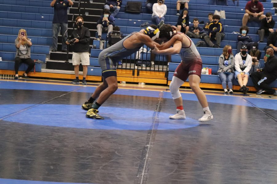 An MSD wrestler faces off an opponent in the BCAA tournament as spectators take pictures and videos. MSD took home a team award for the first time in more than a decade. Photo by Fenthon Aristhomene.