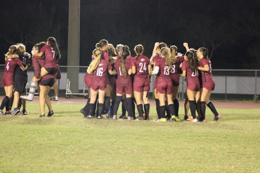The MSD women's varsity soccer team celebrates their 3-2 victory over the Boca Raton Bulls by huddling on the field.