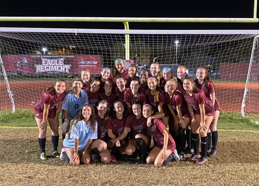 The MSD women's varsity soccer team gathers together at the goalpost after their final game against Cypress Bay for a team photo.