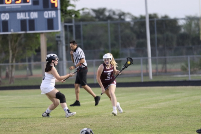 Freshman Gracyn Haynes, a women's varsity lacrosse player at MSD, clears the ball up the field after getting it back from the other team. Photo by Isabelly Silveira