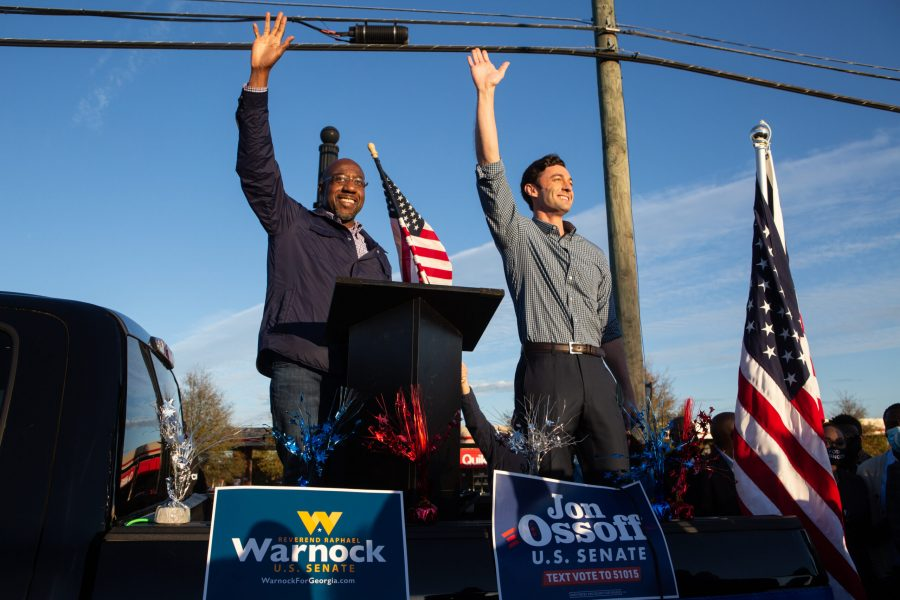 Democratic U.S. Senate candidates Jon Ossoff, right, and Raphael Warnock of Georgia wave to supporters during a rally on Nov. 15, 2020, in Marietta, Georgia. Ossoff and Warnock won their runoff races in January. (Jessica McGowan/Getty Images/TNS)
