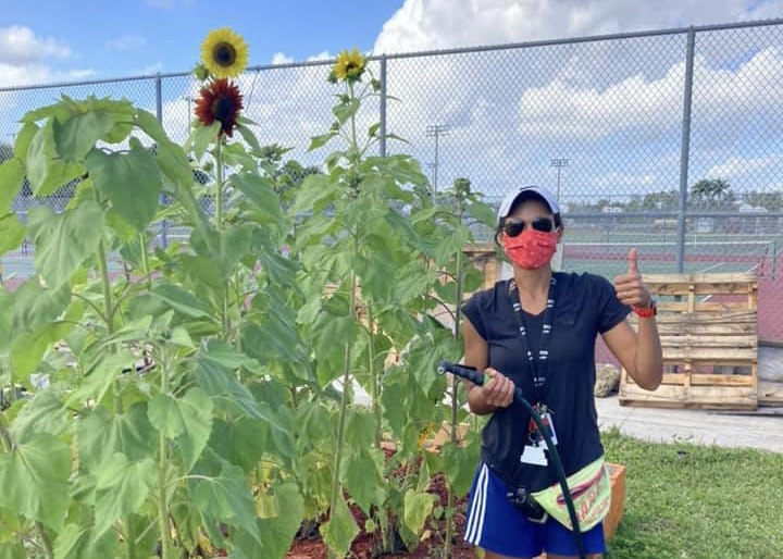 Fitness lifestyle teacher Stephanie Beaty watering sunflowers in Marjory's Garden. Photo courtesy of Stephanie Beaty