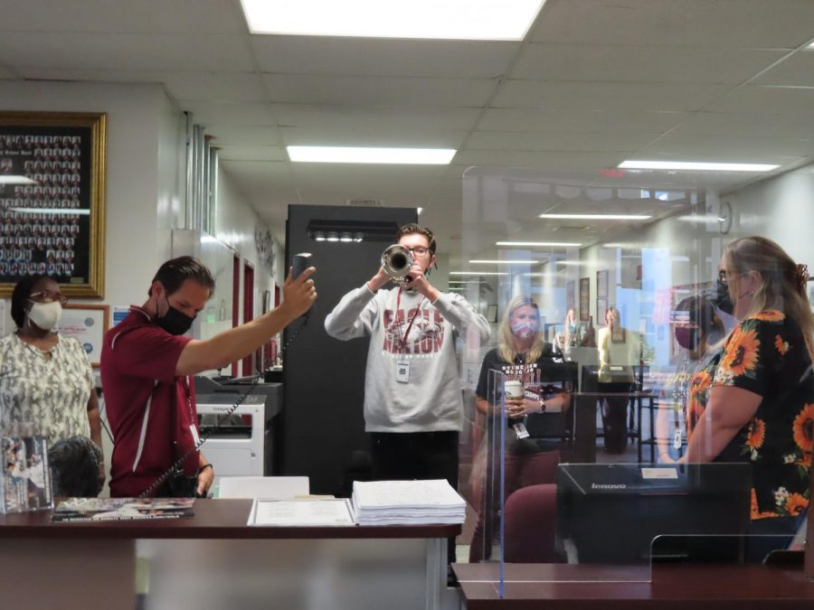 Junior Blake Ogden performs The Star-Spangled Banner while Assistant Principal Daniel Lechtman holds up the intercom.