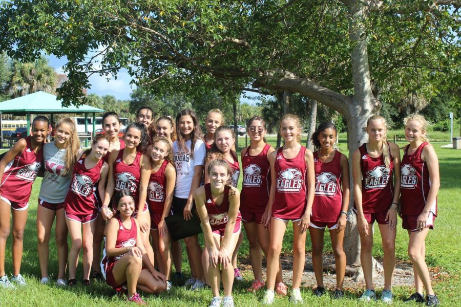 Gabby Fisher and Devyn Sanders gather with the womans cross country team during a meet in the 2019-2020 school year.