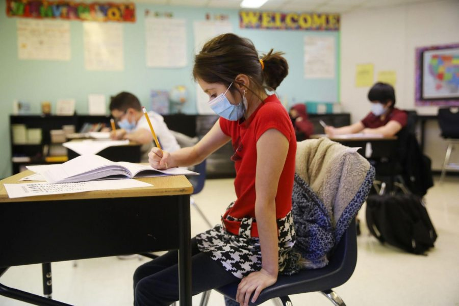 Fifth grader Evelyn Duran works on a writing assignment ONeal Elementary School in Elgin Friday. The district superintendent is among hundreds in Illinois who want standardized testing waived this spring. Photo courtesy of Stacey Wescott