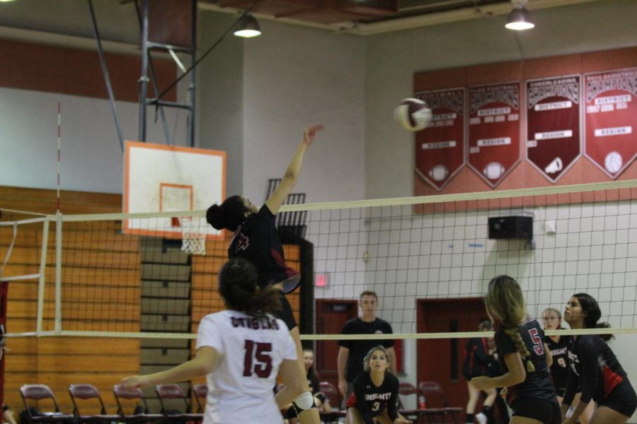 Eagles setter Jordan Robertson (4) spikes the ball onto the Monarch side of the net. Robertson contributed to several points in the game.