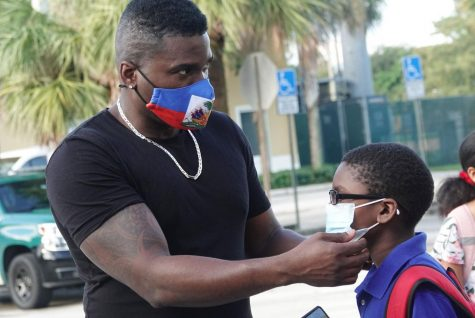 Guyano Dulcio helps his son Tayden, age 8, with his mask before school on Sept. 22 at Tamarac Elementary School. Broward schools continue with a no opt out mask mandate in defiance of Gov. DeSantis. Photo courtesy of Joe Cavaretta