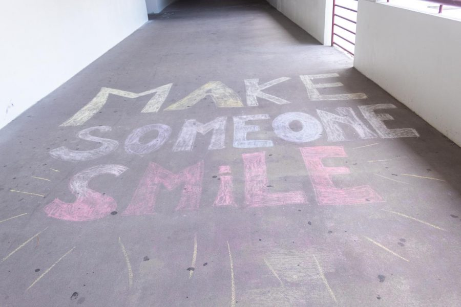 Make someone smile.Peer counseling students write happy chalk messages across campus.